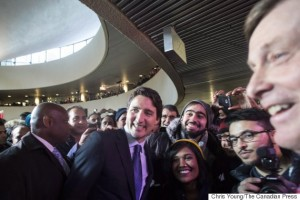 Prime Minister Justin Trudeau (centre) poses for a photo with people in the crowd as Toronto Mayor John Tory (right) looks on holds following a news conference in the rotunda at Toronto City Hall on Wednesday, January 13, 2016. THE CANADIAN PRESS/Chris Young