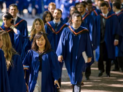Group of graduating students in their gowns, walking in procession