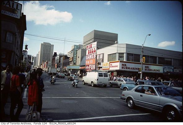 An old photo of the Yonge-Dundas intersection featuring fewer buildings, some cars, and pedestrians.