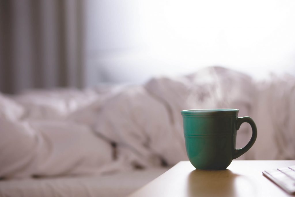 A photo of a coffee cup steaming next to a bed