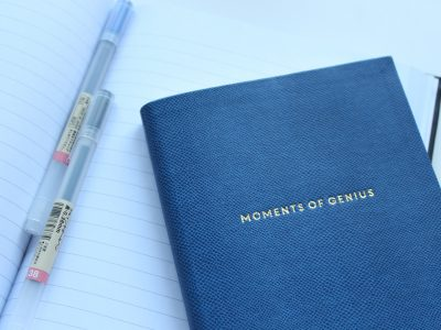 """A couple pens and a blue notebook with the imprint """"Moments of Genius"""" on the front"""
