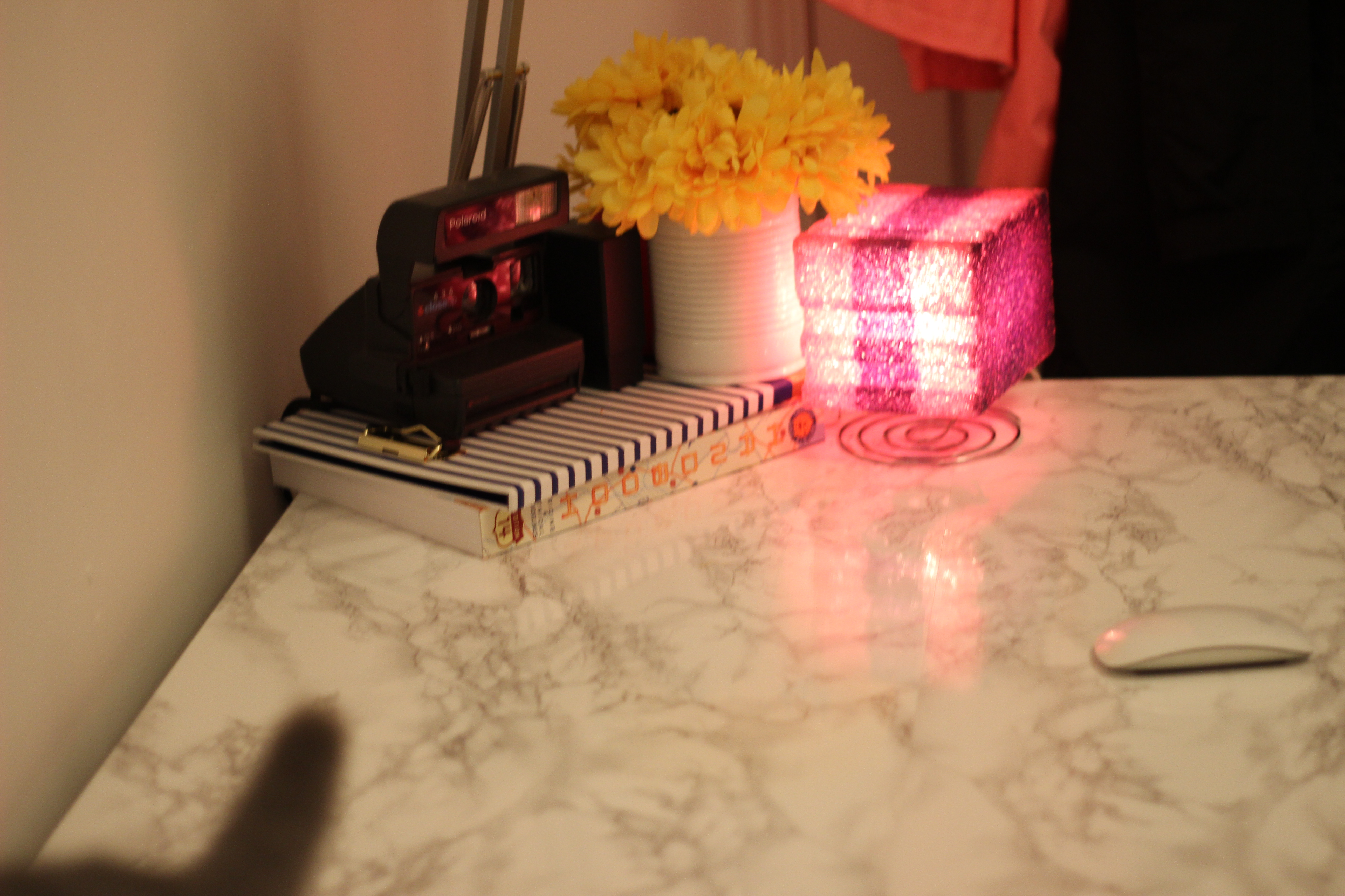 a marble desk with a stack of books, a polaroid camera, lights and flowers