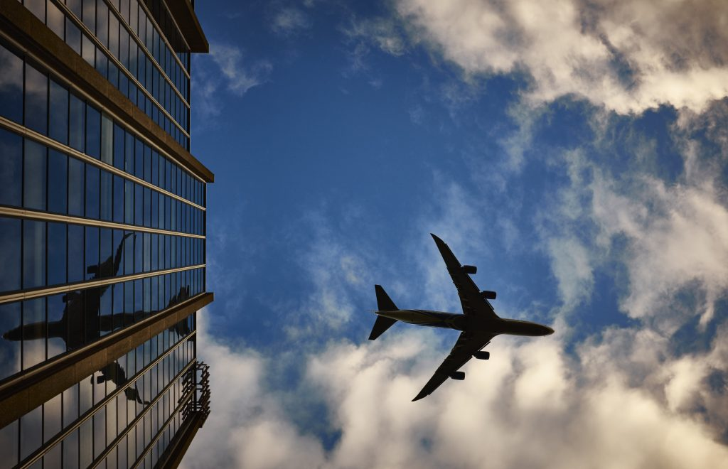 Plane flies over buildings.