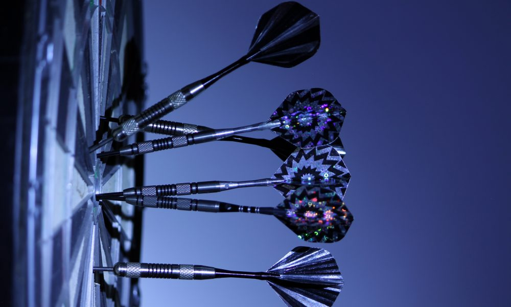 Darts stick out of a dartboard