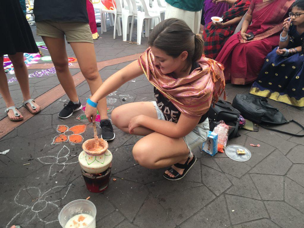 Stef kneels over her pot, cooking