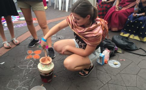 Stef kneels over her pot, cooking