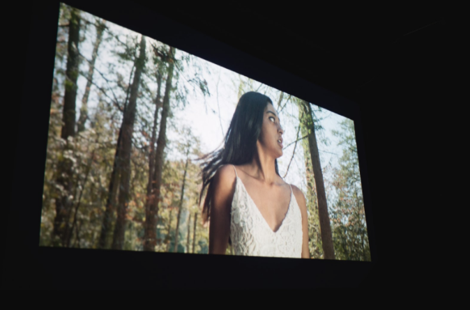 A screen projects an image of a woman in a forest, looking scared