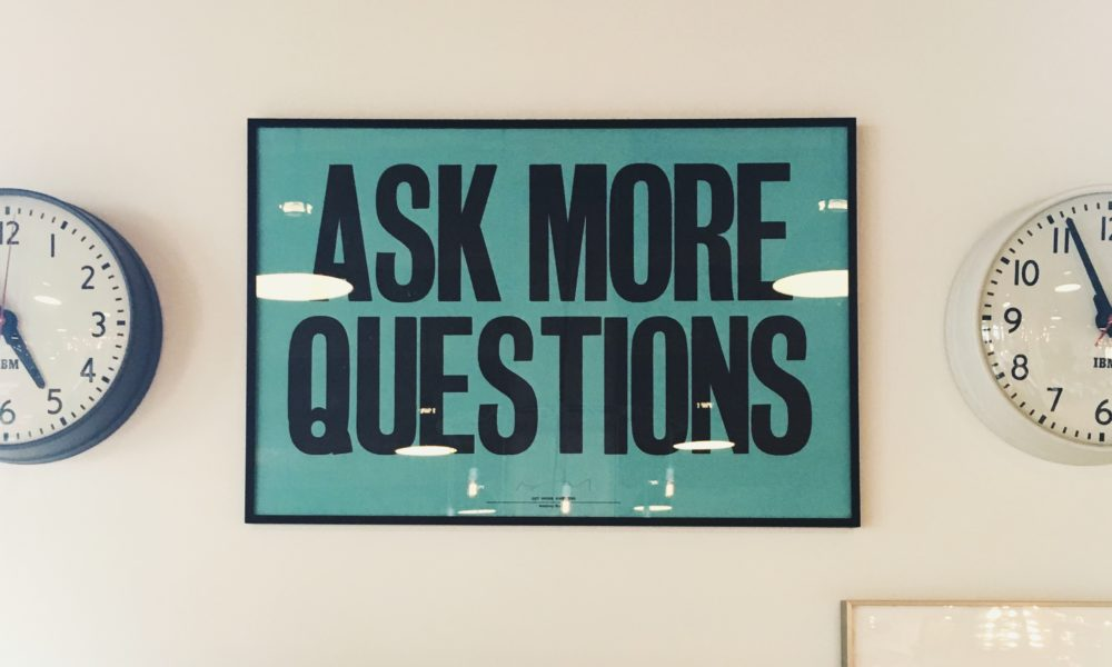 """A poster on a wall says """"Ask More Questions"""""""