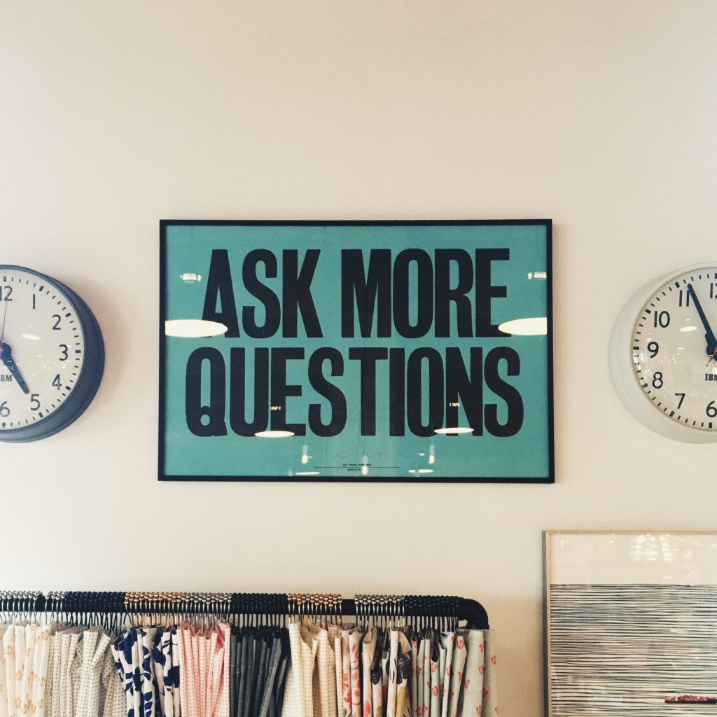 "A poster on a wall says ""Ask More Questions"""