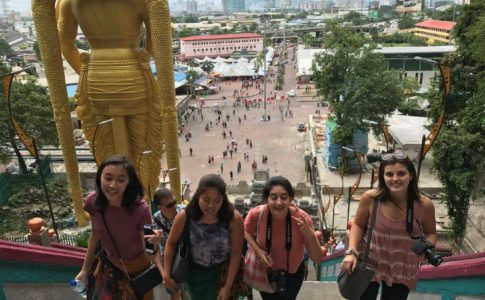 Four girls climb steps at the Batu Caves in Malaysia.