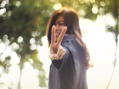 An Asian girl extends the peace sign towards the camera