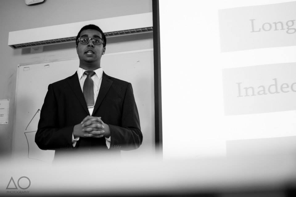 A black and white image of Ali giving a presentation