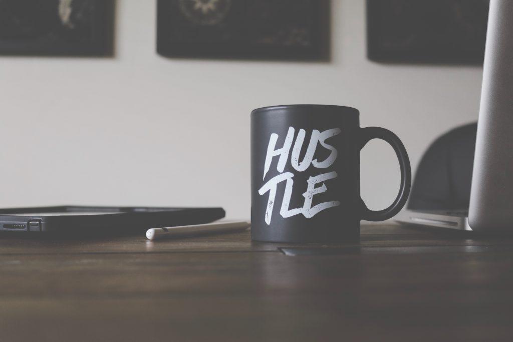 """A coffee mug on a desk with a laptop; the coffee mug says """"HUSTLE"""" on it"""