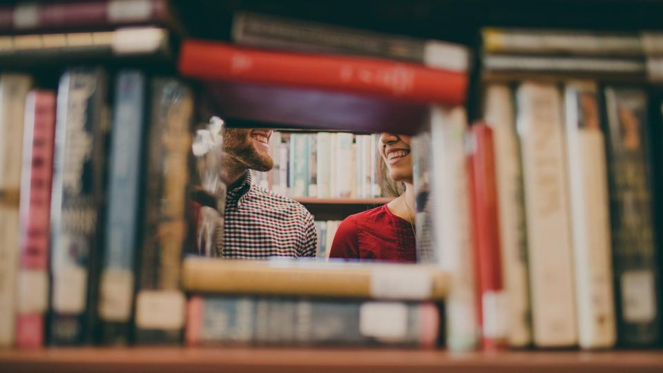 The profile of a man and woman looking at each through the frame of library books.