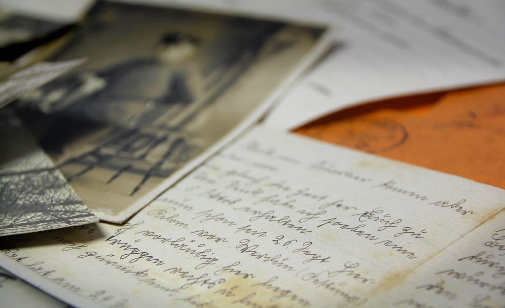 An old photograph and handwritten letter spread across a desk