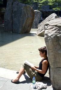 girl sitting at lake devo reading a book
