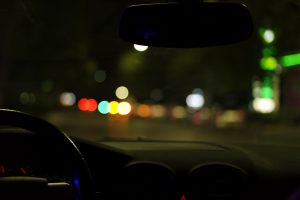 A photo of a city street at night through the windshield and dashboard of a car.