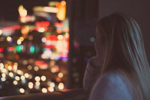 A girl looking out the window at a cityscape at night