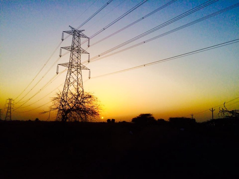 a photo of powerlines over a yellow sky