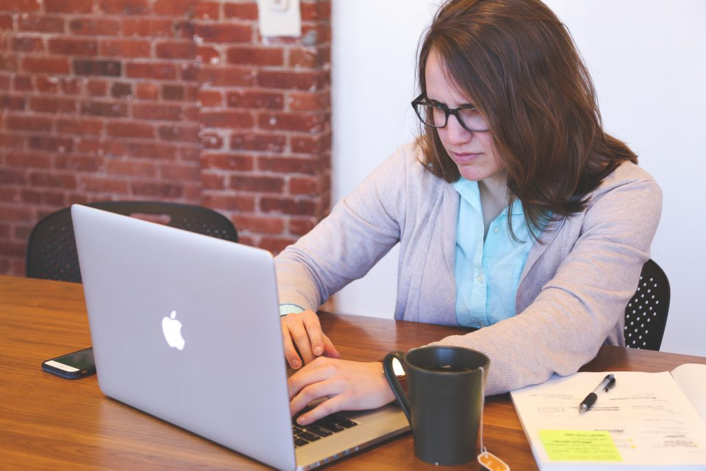 Woman looks frustrated while working on laptop.