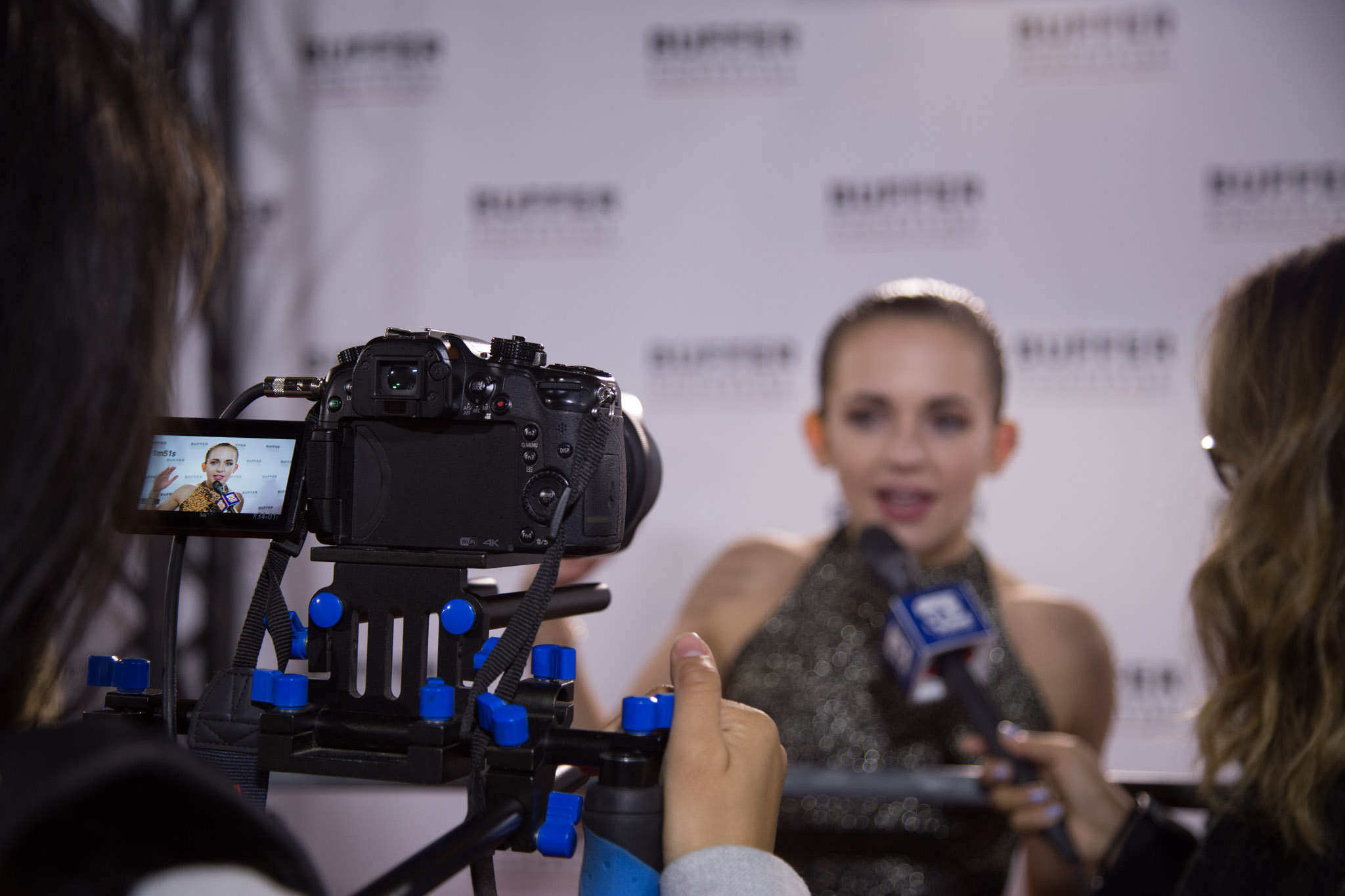 An over-the-shoulder shot of RU Student Life shooting an interview on the red carpet