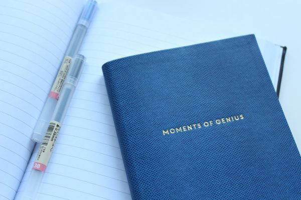 "A couple pens and a blue notebook with the imprint ""Moments of Genius"" on the front"