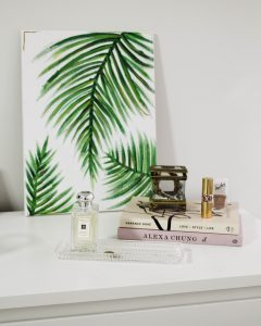 a painting, a couple of books, perfume and makeup sitting on a white desk
