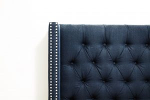 a close up of a dark navy chair against a white wall