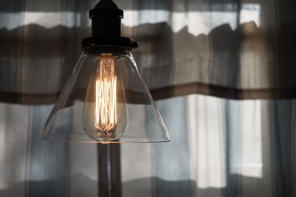 An image of a lightbulb in front of curtains