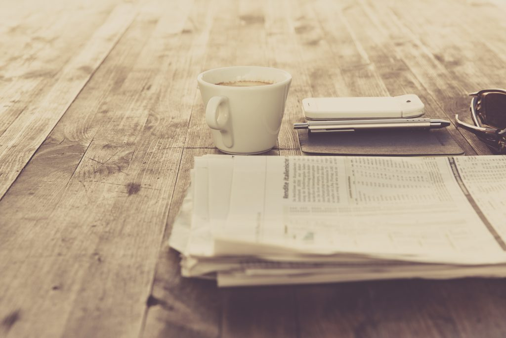 A photo of a cup of coffee, phone, and newspaper laid out on a table.