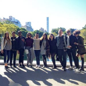 a group of friends in front of a lake in central park