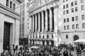 black and white photo of a building in wall street with crowds of people in front of it