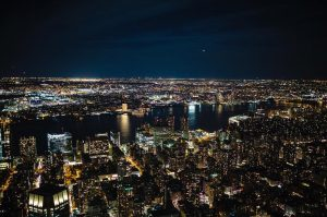 a cityscape shot of New York city at night with many buildings and the Brooklyn Bridge