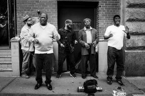 a black and white wide shot of 5 performers on the streets of New York City, singing and expressing emotion with a backpack on the ground