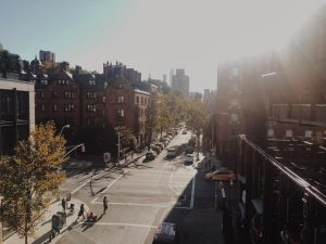 a view from above the chelsea highline of a street in Soho with cars and people on the road