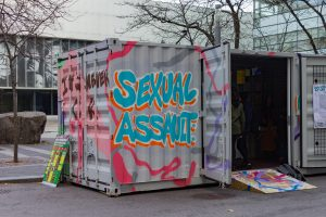 "spray paint of the words ""sexual assault"" on the side of the Lost Words live artshow exhibit"