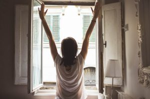 A girl stands in front of a window, arms outstretched