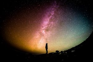 A person against a colourful night sky
