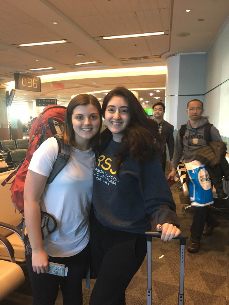 Stefanie and her friend prepare to board their flight, with big backpacks on!