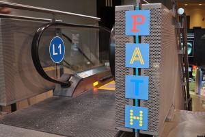 a PATH underground sign next to an escalator