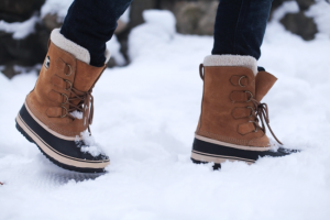 person wearing brown winter boots in the snow