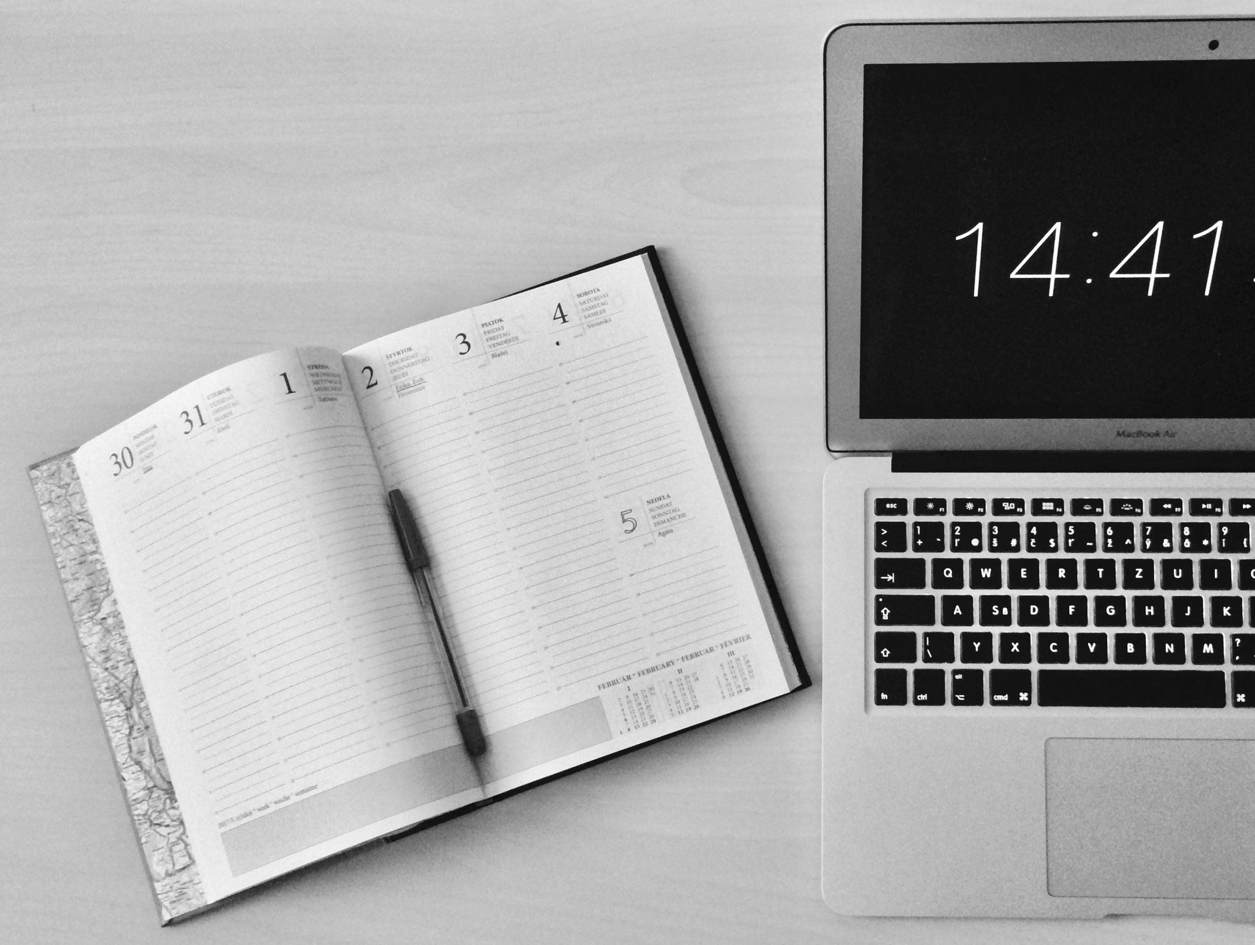 """A laptop reads """"14:41"""" and an open calendar sit on a desk."""