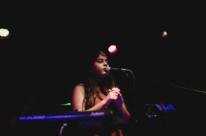 A female performer sings on stage into a microphone
