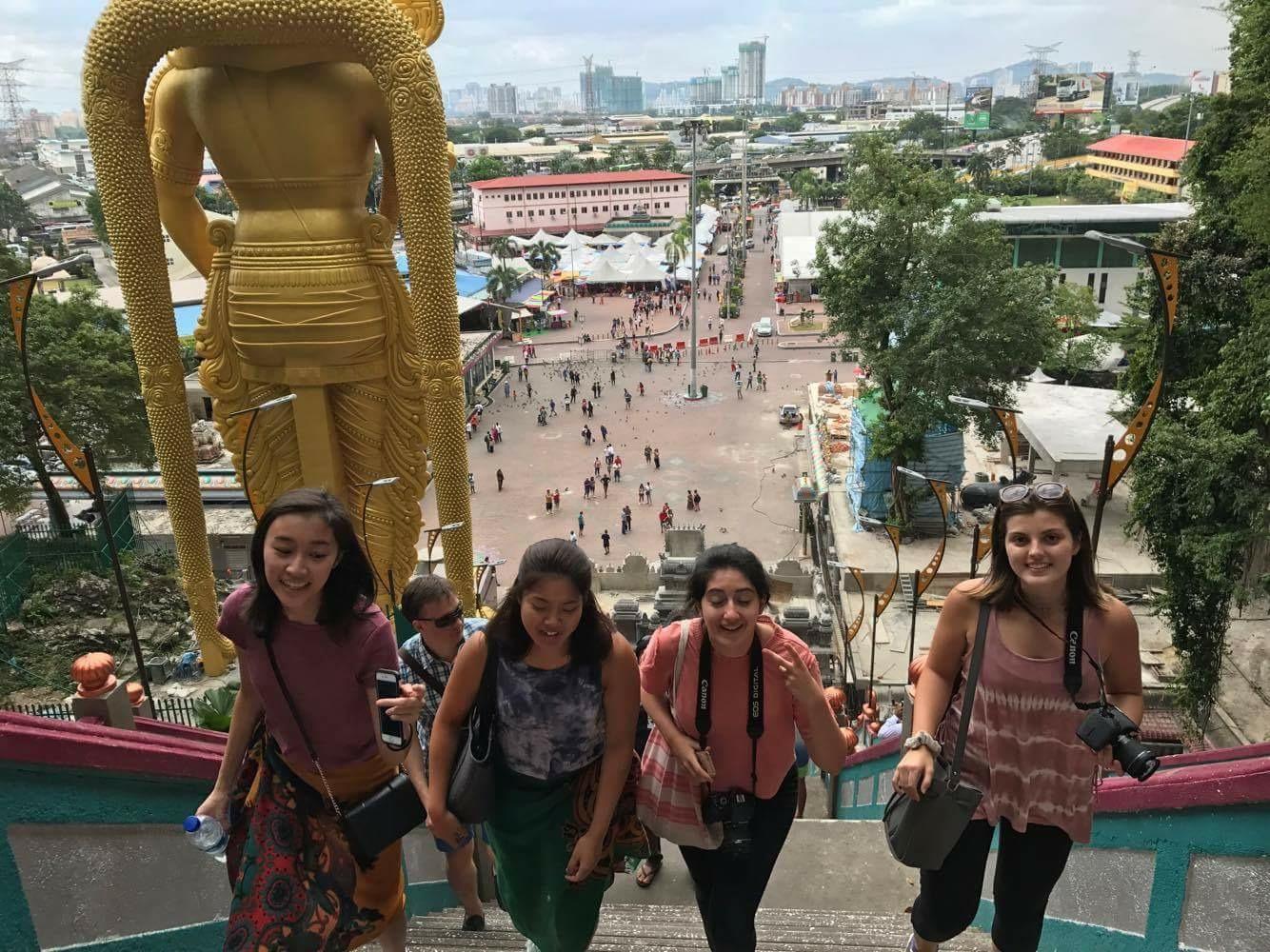 Four girls climb steps at the Batu Caves in Malaysia.
