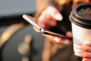 A girl holds a coffee and her phone