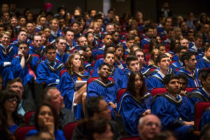 A group of graduates in their cap and gown in the theatre for convocation