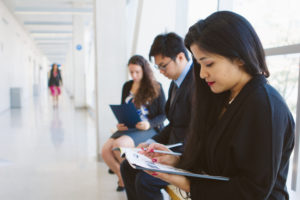 Students wait for an interview in a bright hallway