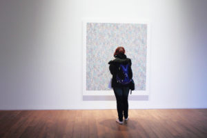 A girl faces a painting on a wall and looks at it