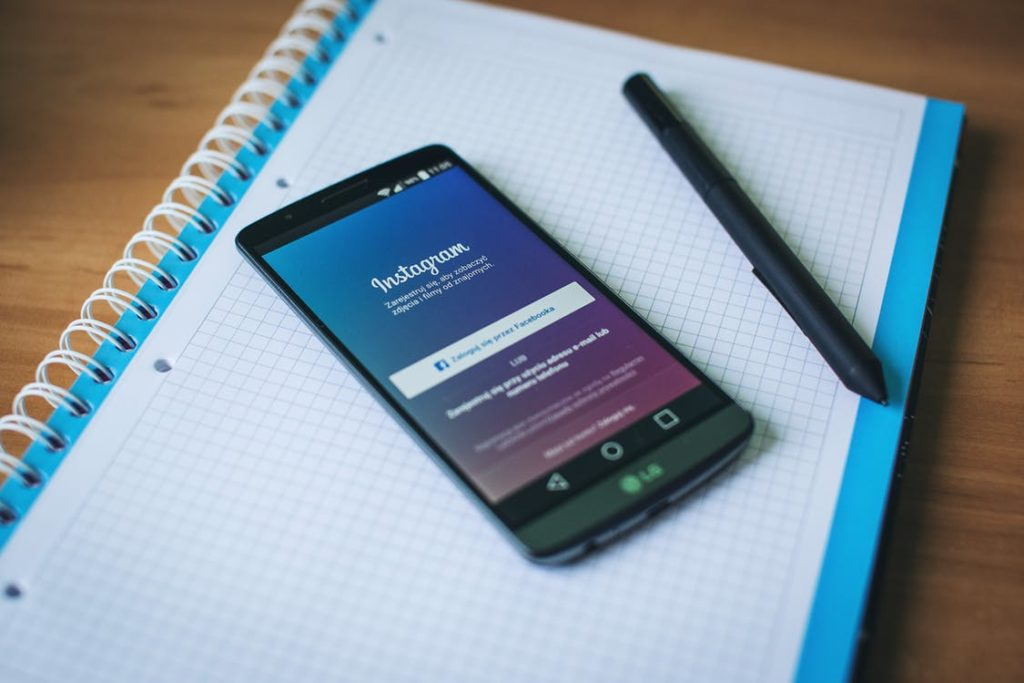 phone sitting on a notepad with Instagram opened on it