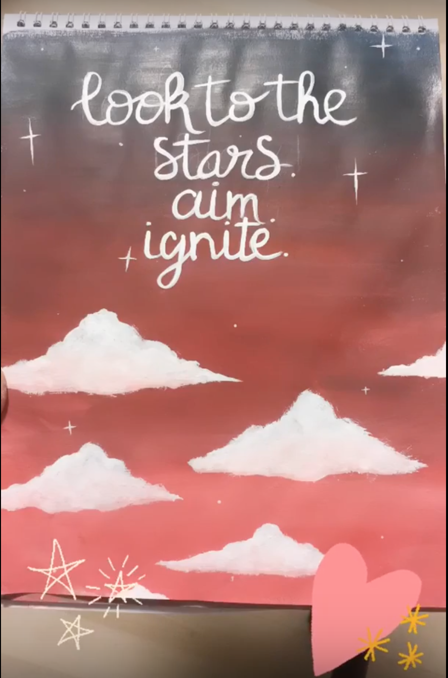 "A painting with a pink and grey background with white fluffy clouds and the words ""look to the stars. aim. ignite."""